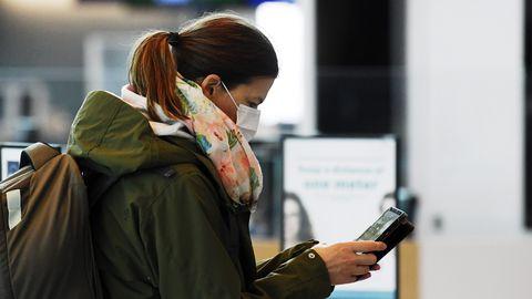 Näomaski kandev reisija vaatab Helsingi rahvusvahelises lennujaamas Vantaas telefoni.